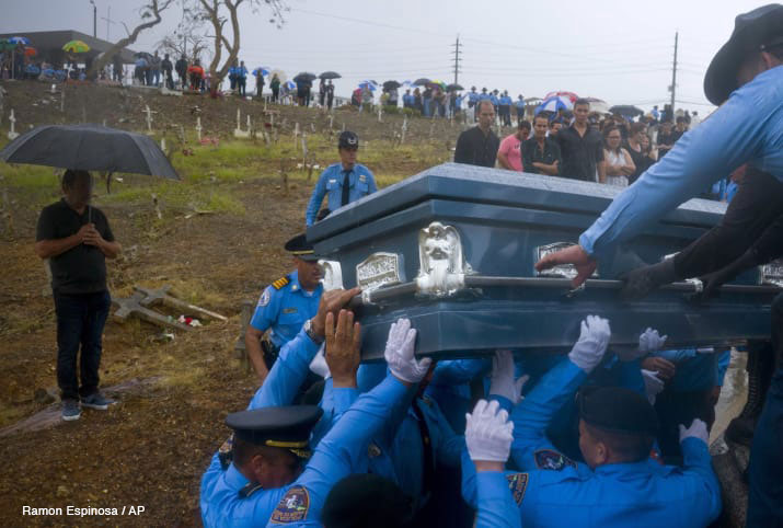 Police lift the coffin of fellow officer Luis Angel Gonzalez Lorenzo, who was killed while trying to cross a river in his car during Hurricane Maria.